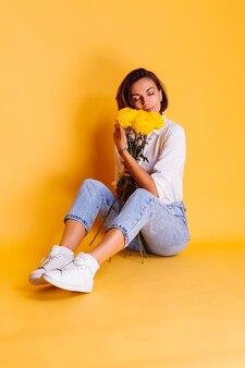 Estúdio, tiro em fundo amarelo. mulher caucasiana feliz, cabelo curto, vestindo roupas casuais, camisa branca e calça jeans, segurando um buquê de ásteres amarelos