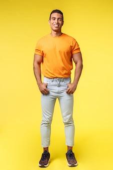 Estúdio vertical completo tiro cara jovem hippie com corpo mascular, t-shirt laranja e calça branca, de mãos dadas nos bolsos, sorrindo câmera satisfeito e confiante, pose casual
