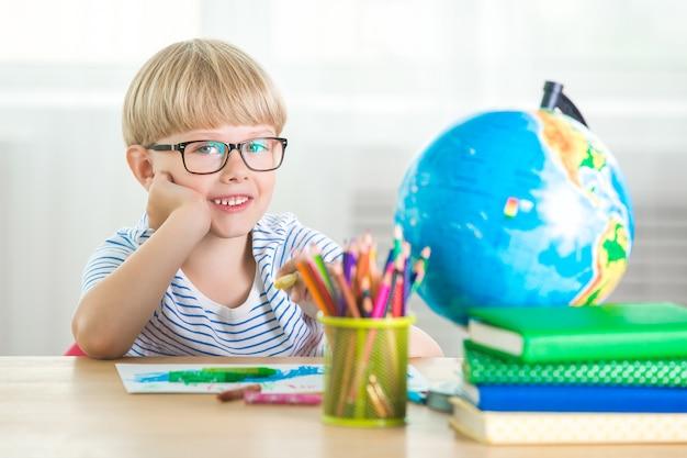 Estudo de criança bonito em casa. garotinho com globo e livros dentro de casa. adorável aluno aprendendo lições e realizando tarefas