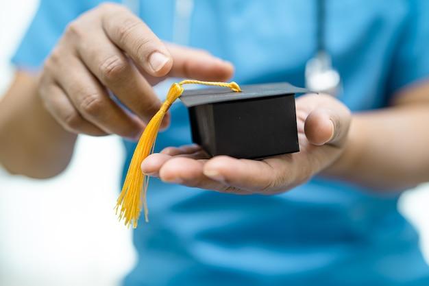 Estudo de médico asiático aprende com chapéu de lacuna de graduação no hospital
