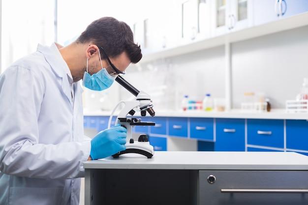 Estudo de sucesso. ambicioso e habilidoso assistente de laboratório masculino em pé de perfil enquanto examina a amostra e usa o microscópio