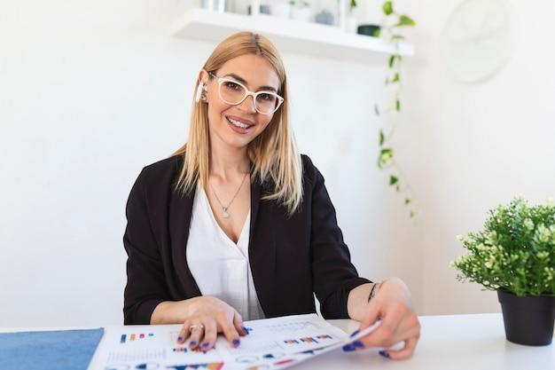 Estudo jovem sorridente em casa com o laptop, pesquisa on-line para cursos, conceito de e-learning de educação on-line, mulher de negócios jovem tendo chamada em conferência com o cliente no laptop.