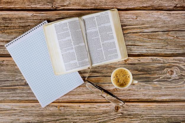 Estudo pessoal da bíblia sagrada com uma xícara de café em cima de uma mesa com óculos, bloco de notas em espiral