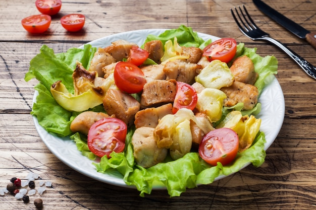 Estufado de pedaços de frango com legumes em um prato.