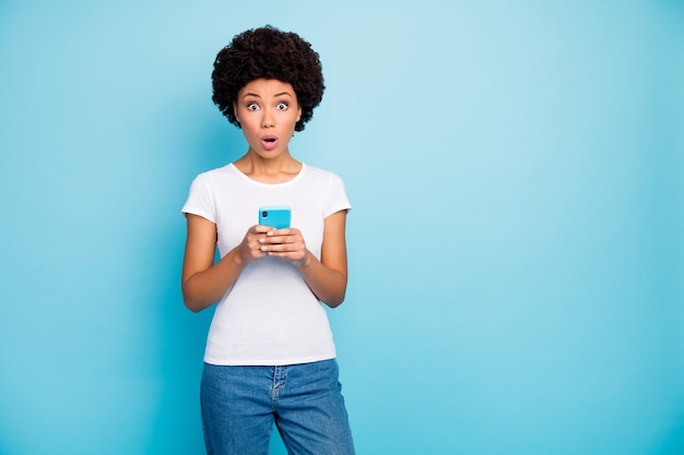Estupor linda senhora segurando aplicativo de telefone com as mãos boca aberta