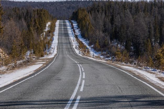 Esvazie a estrada de enrolamento pavimentada através da floresta do inverno na montanha com voltas e curva e neve na borda da estrada.