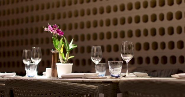 Esvazie a mesa de servir em um restaurante esperando por convidados óculos e flor na mesa