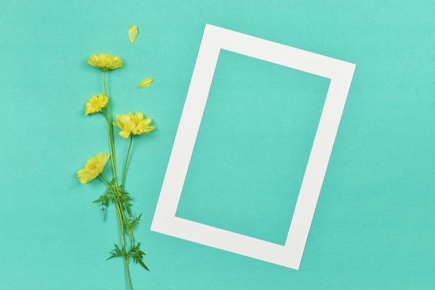Esvazie a moldura de papel de foto em branco com uma flor amarela no lado.