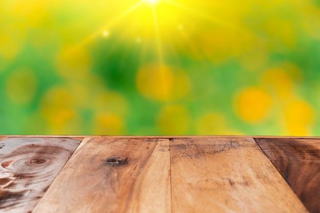 Esvazie a placa de madeira velha no campo de flores da natureza do borrão para o produto da mostra.
