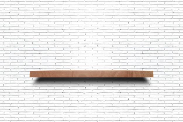 Esvazie a prateleira de madeira na textura branca velha da parede de tijolo. para produtos de exibição.