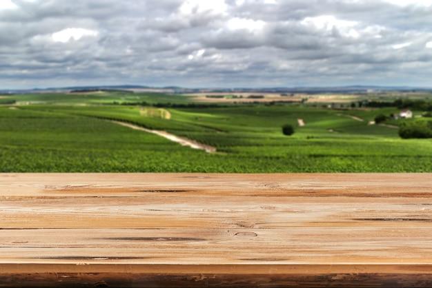 Esvazie a superfície de mesa de madeira dura envelhecida em um fundo natural de campo turva para exibir e montar seus produtos.