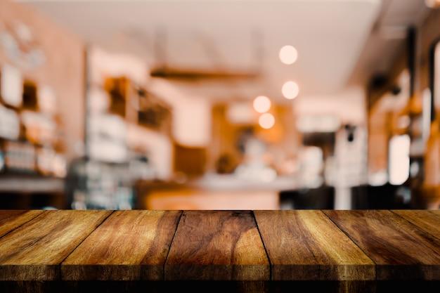 Esvazie a tabela de madeira com a cafetaria ou o café do interior do borrão para o fundo.