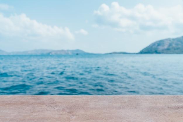 Esvazie a tabela de madeira com partido no fundo borrado praia nas horas de verão.