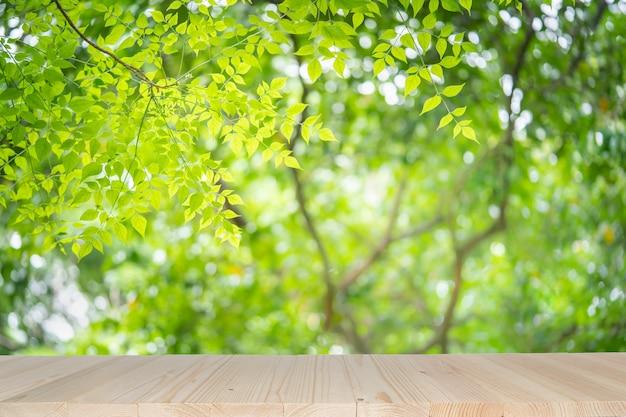 Esvazie a tabela de madeira no fundo verde da natureza com bokeh da beleza sob a luz solar.