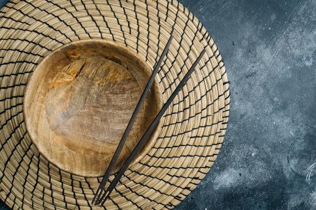 Esvazie a tigela de madeira (tigela de bambu vazia) com pauzinhos chineses na pedra cinza. conceito de comida asiática