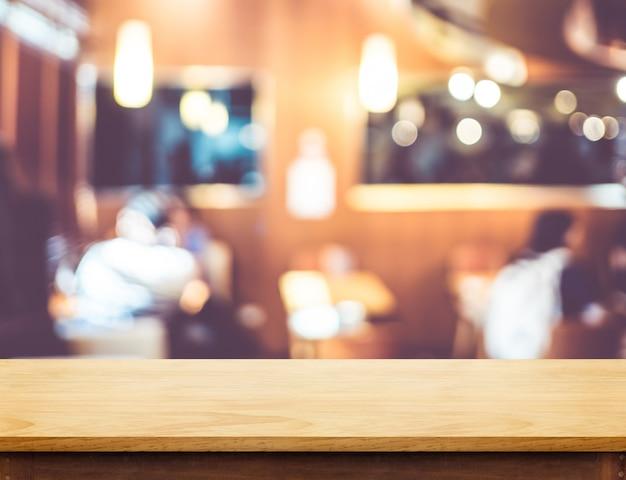 Esvazie o tampo da mesa de madeira marrom no fundo do restaurante de borrão com luz de bokeh
