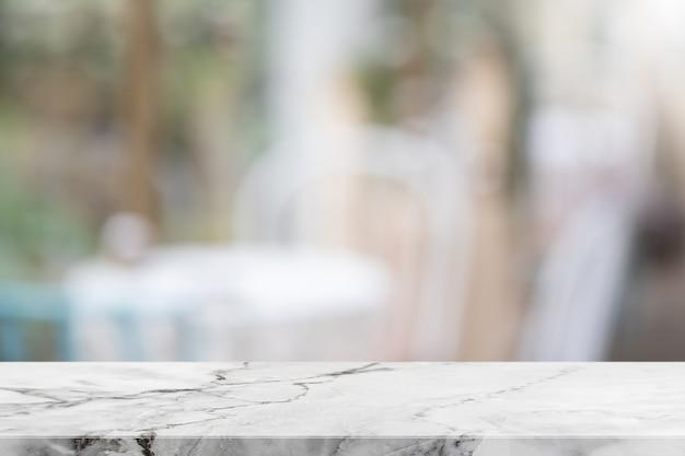 Esvazie o tampo da mesa de mármore de pedra branca e borrou do restaurante interior com fundo do fundo do jardim da opinião da janela.