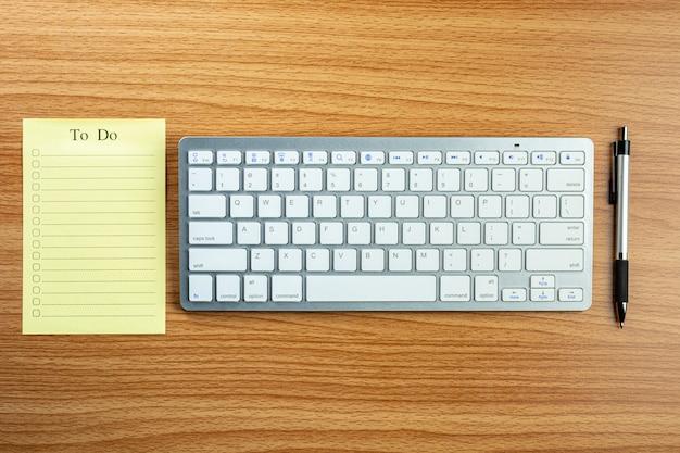 Esvazie para fazer a lista e um teclado de computador, pena na mesa de madeira.