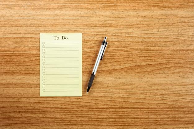 Esvazie para fazer a lista e uma caneta na mesa de madeira.