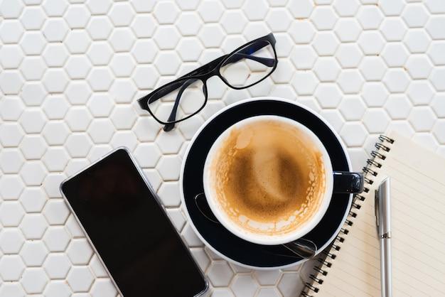 Esvazie uma xícara de café na mesa branca