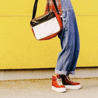 Etapa no outono. snekers e bolsa vermelhos elegantes. moda urbana