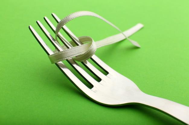 Etapas de amarrar o arco no garfo na mesa verde, close-up