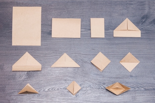 Etapas de fazer origami barco de papel com fundo de madeira.