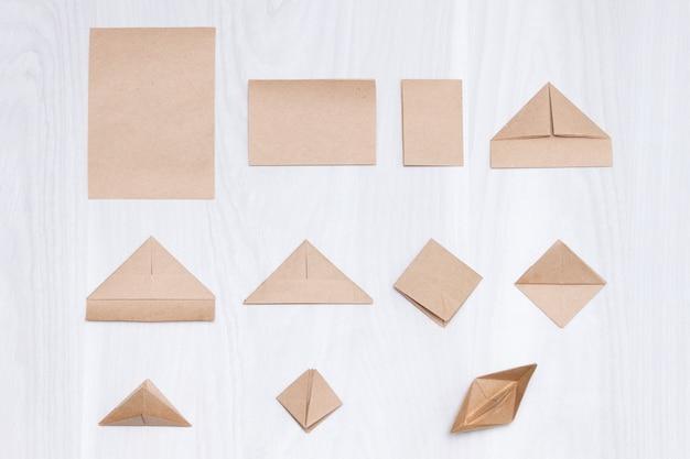 Etapas de fazer origami barco de papel em fundo branco de madeira.