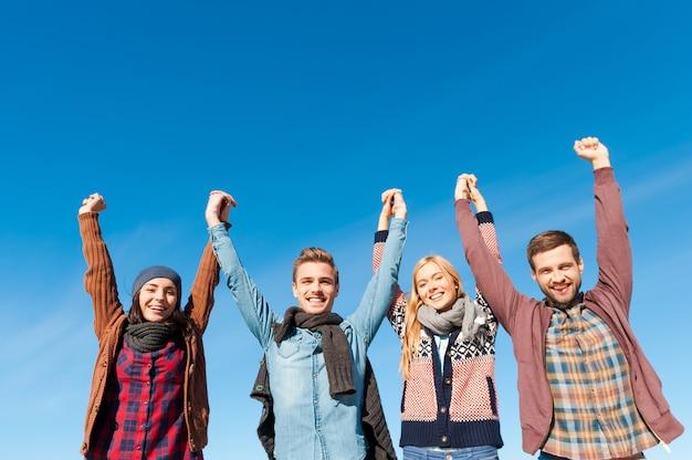 Eternamente jovem. vista de baixo ângulo de quatro jovens felizes de mãos dadas e levantando-as com o céu azul como pano de fundo