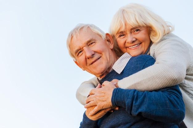 Eternamente jovem. vista de baixo ângulo de um casal feliz de idosos se unindo e sorrindo com o céu azul como pano de fundo