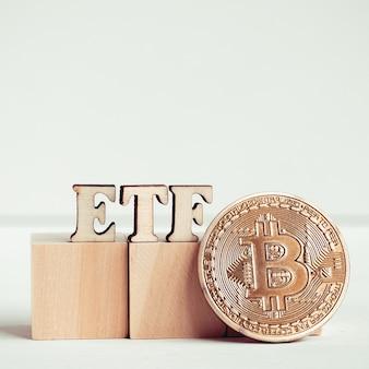 Etf letras de madeira ao lado de uma moeda de bitcoin.