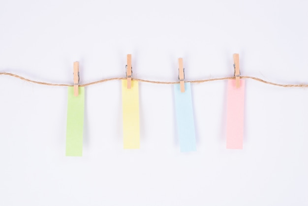 Etiqueta adesiva colorida pendurada em fundo branco isolado de corda