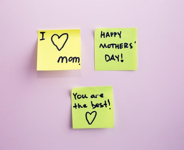 Etiqueta amarela do lembrete da nota do dia de mãe feliz em uma parede,