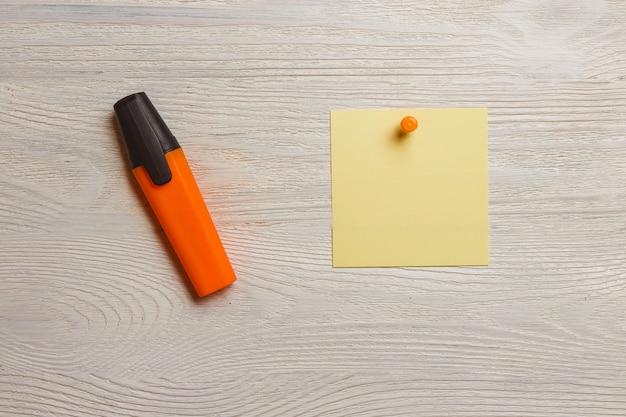 Etiqueta amarela estacionária, em branco, pushpins alaranjados, marcador na placa de madeira branca.