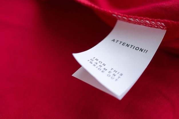 Etiqueta branca de instruções de lavagem de roupas para lavar roupas em camisa de algodão vermelha
