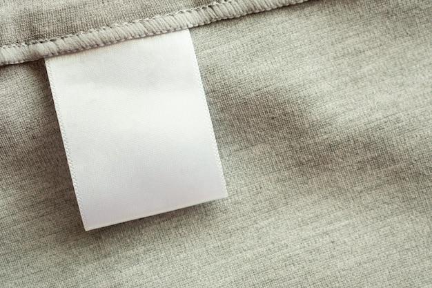 Etiqueta branca em branco da roupa para lavar roupas em fundo de textura de tecido cinza