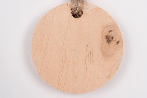Etiqueta da marca de madeira em fundo branco. foto colorida de uma etiqueta de madeira com uma corda
