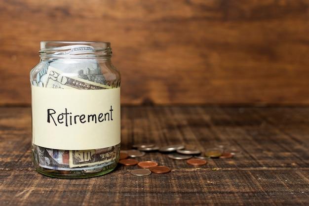 Etiqueta de aposentadoria em uma jarra cheia de dinheiro e cópia espaço
