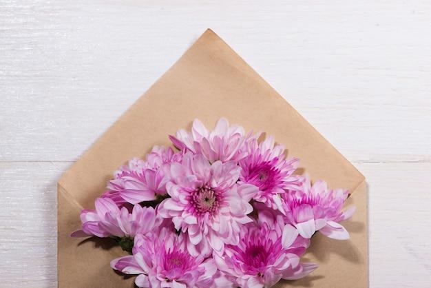 Etiqueta de papel branco em branco com envelope marrom e flores cor de rosa na mesa de madeira.