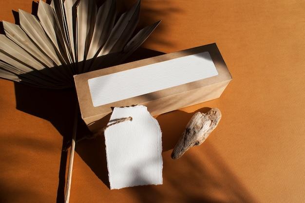 Etiqueta de papel diy e caixa de presente artesanal com folhas de palmeira secas na mesa de terracota texturizada. elegante modelo moderno para identidade de marca. vista plana, vista superior