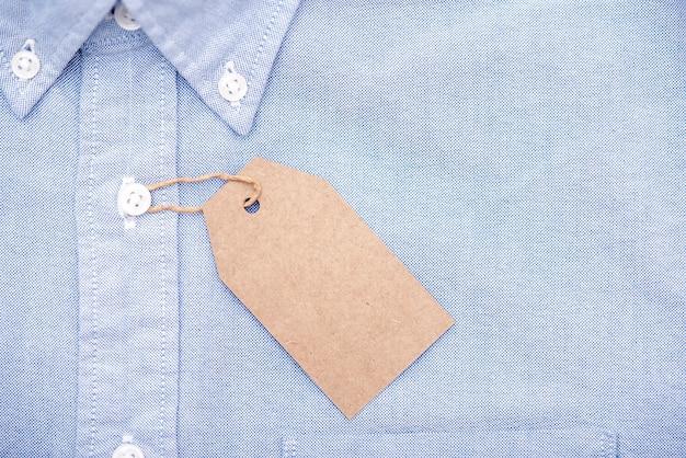 Etiqueta de papel em branco ou etiqueta em cima da camisa azul, espaço para texto