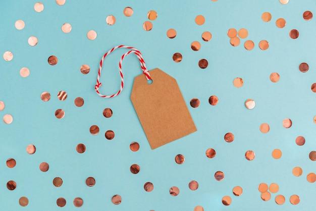 Etiqueta de papel ofício de natal na mesa azul com confetes de coral.