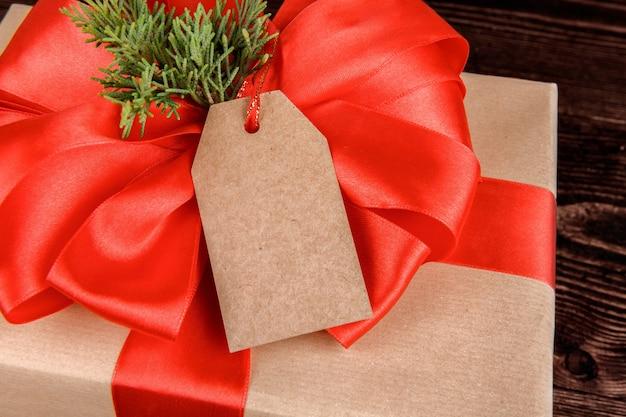 Etiqueta de presente de natal. pacote de presente embrulhado de papel ofício com tag dom, close-up.