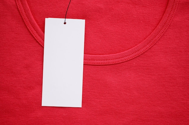 Etiqueta de roupa branca em branco na nova camisa vermelha