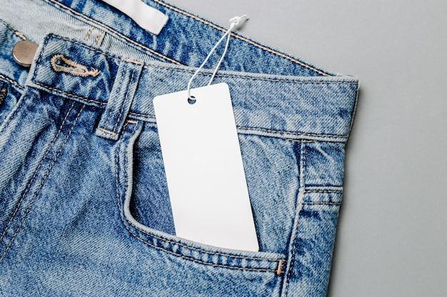 Etiqueta de roupa vazia branca, maquete de etiqueta em branco para desenho em um jeans