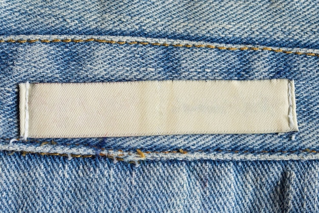 Etiqueta de roupas de lavagem branca em branco sobre fundo de textura de jeans