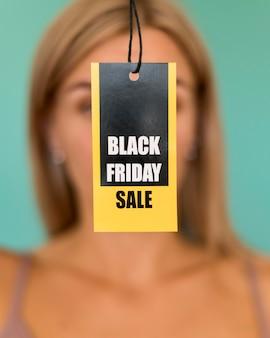 Etiqueta de venda de sexta-feira negra em mãos de mulher desfocada