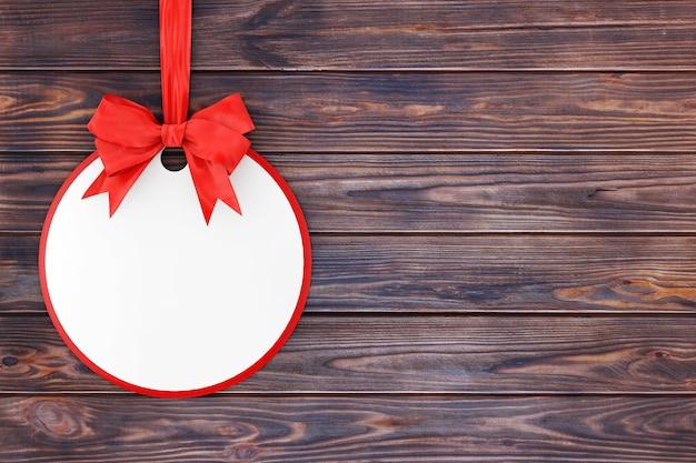 Etiqueta de venda do círculo em branco com fita vermelha e arco em uma mesa de madeira. renderização 3d