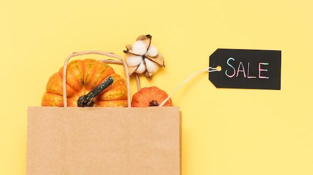 Etiqueta de venda escura com sacola de compras com abóboras em fundo amarelo