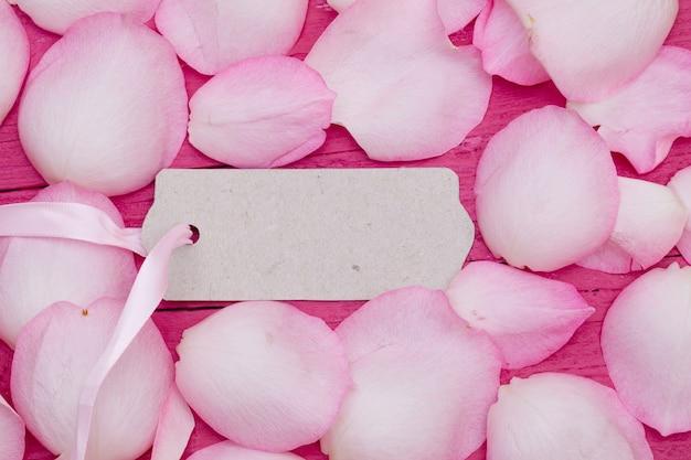 Etiqueta em branco cercada por pétalas de rosa rosa